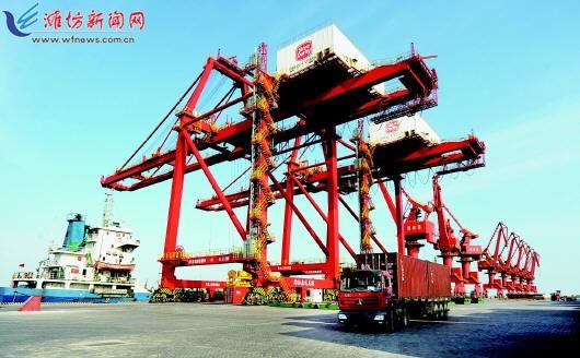 7月10日,在潍坊森达美港集装箱码头,一艘靠泊的货轮正在卸载集装箱